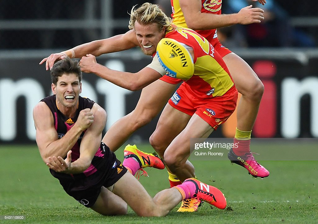 Luke Breust of the Hawks handballs whilst being tackled by Matthew Shaw of the Suns during the round 14 AFL match between the Hawthorn Hawks and the Gold Coast Suns at Aurora Stadium on June 26, 2016 in Launceston, Australia.