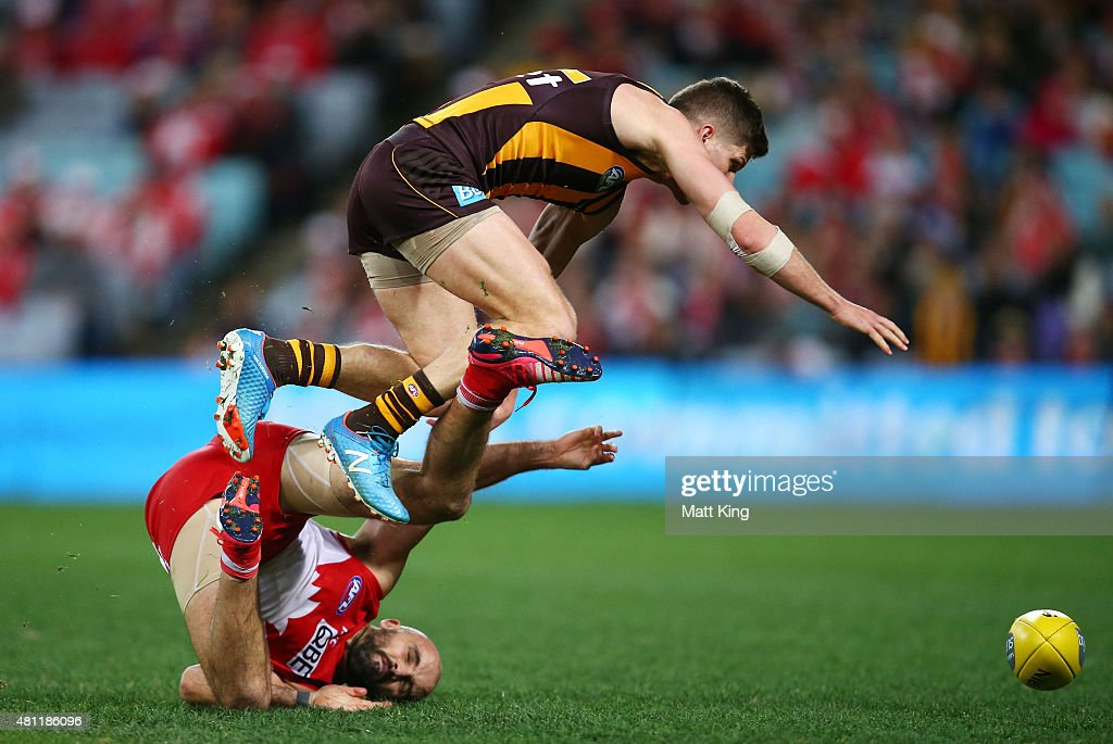 Luke Breust of the Hawks trips over Rhyce Shaw of the Swans during the round 16 AFL match between the Sydney Swans and the Hawthorn Hawks at ANZ Stadium on July 18, 2015 in Sydney, Australia.