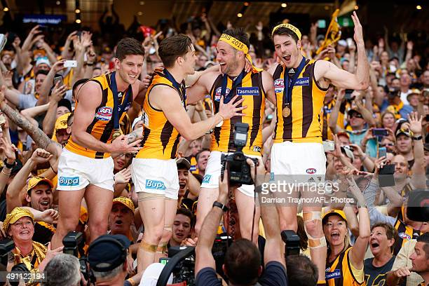 Luke Breust Taylor Duryea Matthew Suckling and Isaac Smith of the Hawks celebrate with fans after the 2015 AFL Grand Final match between the Hawthorn...