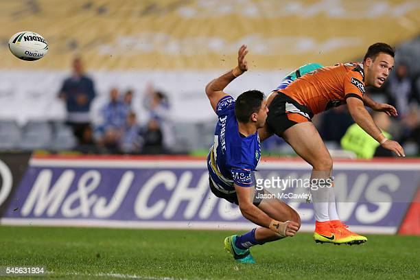 Luke Brooks of the Tigers and Curtis Rona of the Bulldogs compete for the ball during the round 18 NRL match between the Canterbury Bulldogs and the...