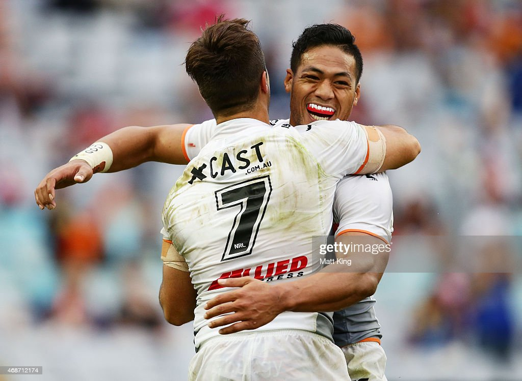 Luke Brooks (L) of the Tigers celebrates with Tim Simona (R) after scoring a try during the round five NRL match between the Parramatta Eels and the Wests Tigers at ANZ Stadium on April 6, 2015 in Sydney, Australia.