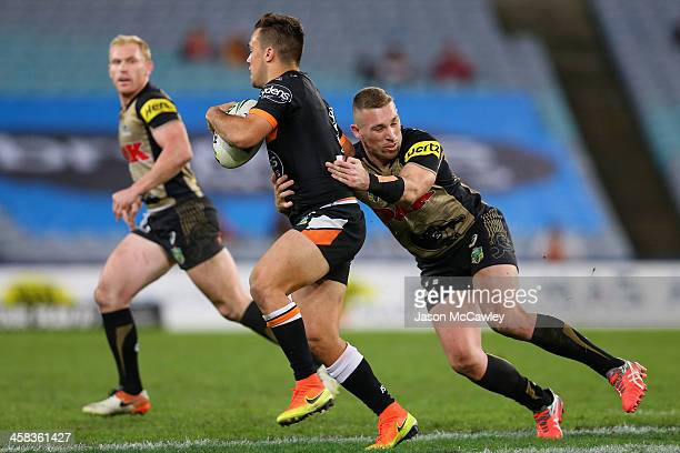 Luke Brooks of the Tigers is tackled by Bryce Cartwright of the Panthers during the round 17 NRL match between the Wests Tigers and the Penrith...