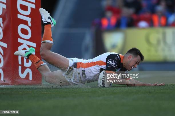 Luke Brooks of the Tigers scores a try during the round 17 NRL match between the Newcastle Knights and the Wests TIgers at McDonald Jones Stadium on...