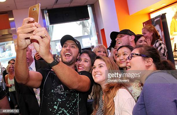 Luke Bryan takes a selfie with fans using the new Galaxy S6 edge at the ATT storein New York to celebrate the unveiling of Samsung's newest devices...