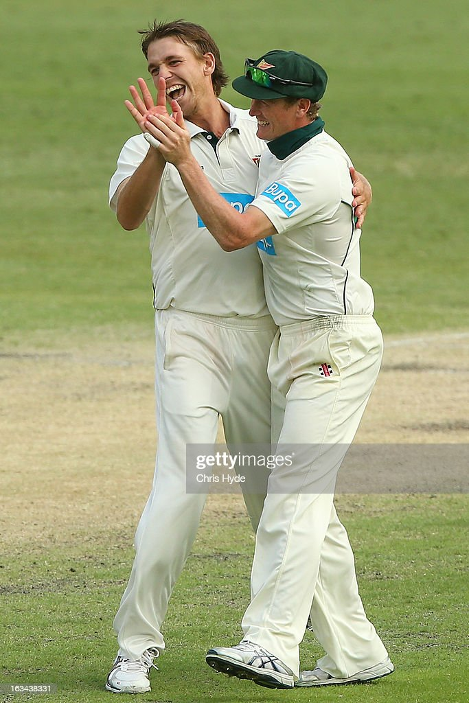 Luke Butterworth and George Bailey of the Tigers celebrate winning on day four of the Sheffield Shield match between the Queensland Bulls and the Tasmanian Tigers at The Gabba on March 10, 2013 in Brisbane, Australia.