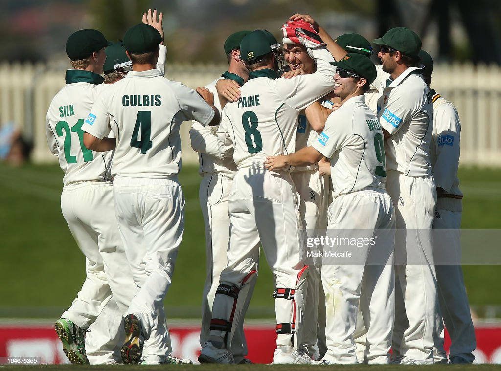 Luke Butterworth of the Tigers celebrates with teammates after taking the wicket of Joe Burns of the Bulls during day five of the Sheffield Shield final between the Tasmania Tigers and the Queensland Bulls at Blundstone Arena on March 26, 2013 in Hobart, Australia.