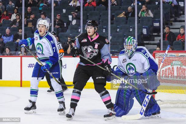 Luke Coleman of the Calgary Hitmen looks for an opening in front of the net of Logan Flodell of the Swift Current Broncos during a WHL game at the...