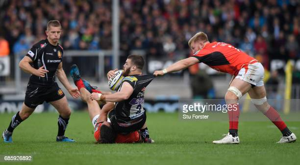 Luke CowanDickie of Exeter Chiefs is tackled by Mike Ellery and Jackson Wray of Saracens during the Aviva Premiership semi final match between Exeter...