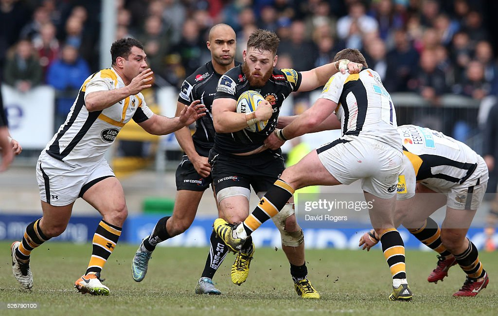Luke Cowan-Dickie of Exeter is tackled by <a gi-track='captionPersonalityLinkClicked' href=/galleries/search?phrase=Matt+Mullan&family=editorial&specificpeople=705828 ng-click='$event.stopPropagation()'>Matt Mullan</a> (R) and George Smith during the Aviva Premiership match between Exeter Chiefs and Wasps at Sandy Park on May 1, 2016 in Exeter, England.