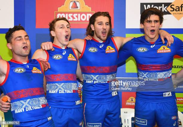 Luke Dahlhaus Bailey Dale Marcus Bontempelli and Lewis Young of the Bulldogs sing the song in the rooms after winning the round 19 AFL match between...