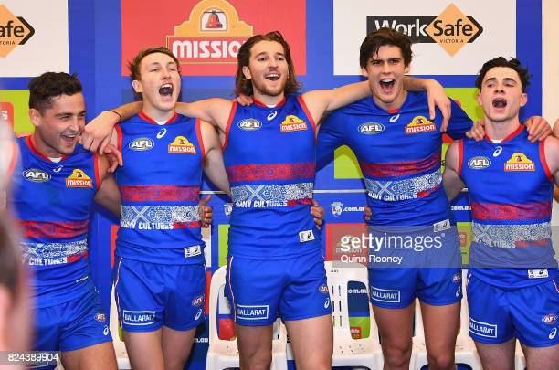 Luke Dahlhaus Bailey Dale Marcus Bontempelli Lewis Young and Toby McLean of the Bulldogs sing the song in the rooms after winning the round 19 AFL...