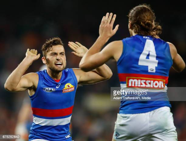 Luke Dahlhaus of the Bulldogs celebrates with Marcus Bontempelli of the Bulldogs during the 2017 AFL round 06 match between the GWS Giants and the...