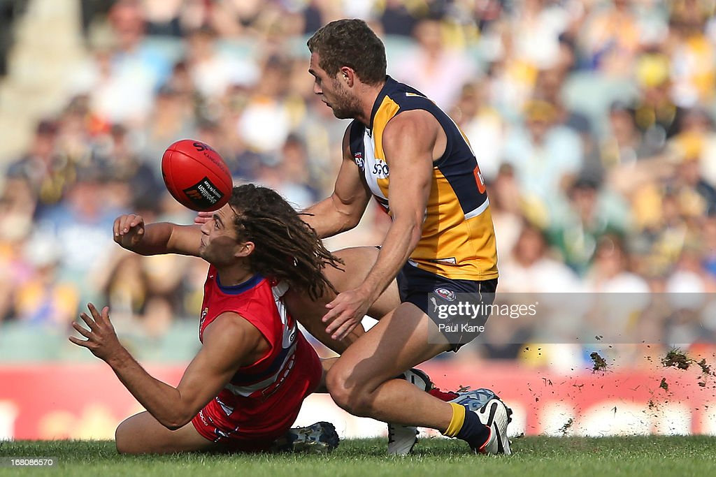 Luke Dahlhaus of the Bulldogs handballs against Jacob Brennan of the Eagles during the round six AFL match between the West Coast Eagles and the Western Bulldogs at Patersons Stadium on May 5, 2013 in Perth, Australia.