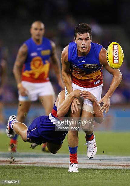 Luke Dahlhaus of the Bulldogs tackles Tom Rockliff of the Lions during the round one AFL match between the Western Bulldogs and the Brisbane Lions at...