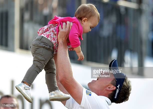 Luke Donald of England lifts up his daughter Elle following his victory in a playoff on the 18th green during the final round of the BMW PGA...