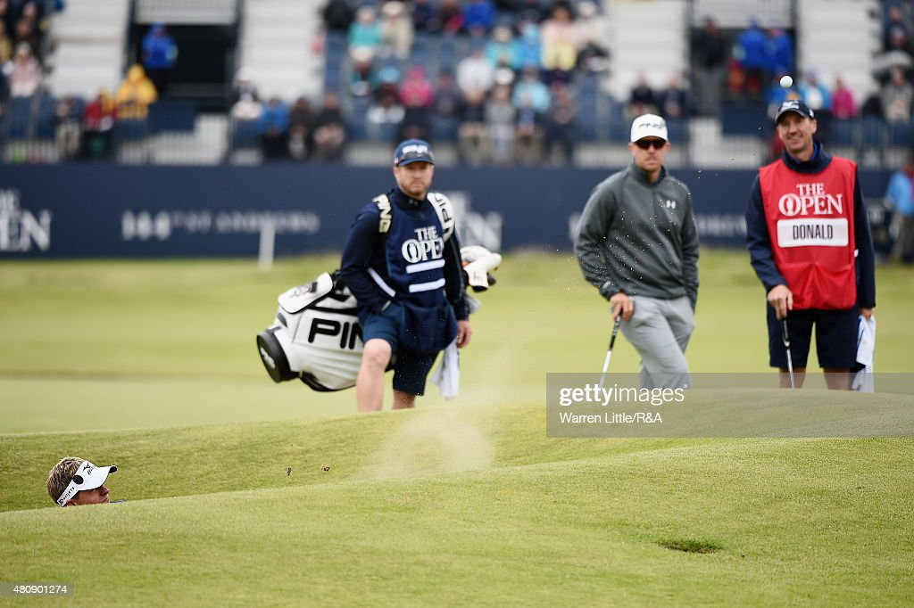 Luke Donald (L) of England plays out of the 17th greenside bunker as Hunter Mahan (2nd R) of the United States, caddie John McLaren (R) and caddie John Wood (2nd L) look on during the first round of the 144th Open Championship at The Old Course on July 16, 2015 in St Andrews, Scotland.