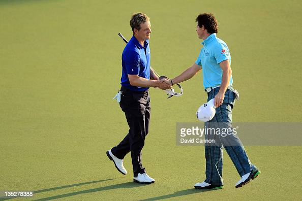 Luke Donald of England shakes hands with his playing partner Rory McIlroy of Northern Ireland at the end of their first round of the Dubai World...