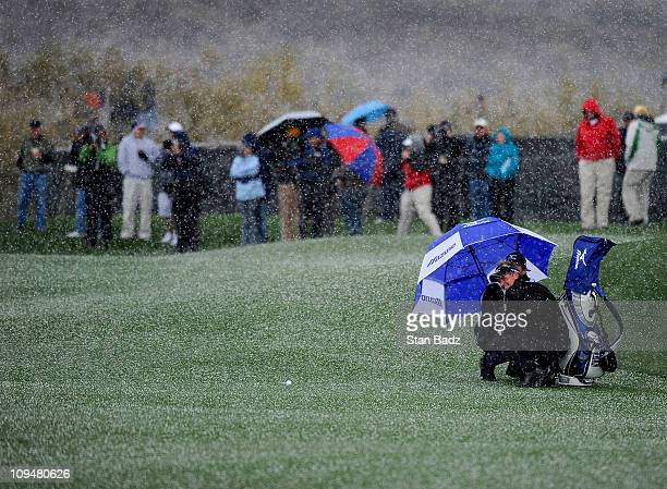 Luke Donald of England smiles as he takes cover under his umbrella from falling snow on the fourth hole during the final round of the World Golf...