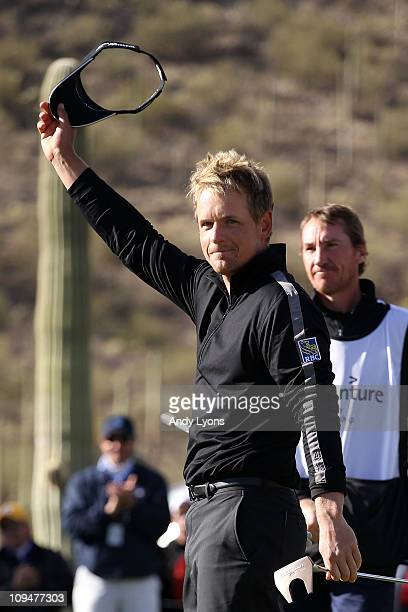 Luke Donald of England waves to fans after winning his match 3up over Martin Kaymer of Germany as his caddie John McLaren looks on during the final...
