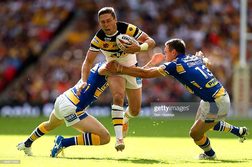 Luke Dorn of Castleford is tackled by Liam Sutcliffe (L) and Kevin Sinfield (R) of Leeds during the Tetley's Challenge Cup Final between Leeds Rhinos and Castleford Tigers at Wembley Stadium on August 23, 2014 in London, England.