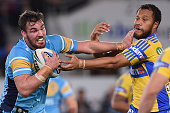 Luke Douglas of the Titans is tackled during the round 21 NRL match between the Gold Coast Titans and the Parramatta Eels at Cbus Super Stadium on...