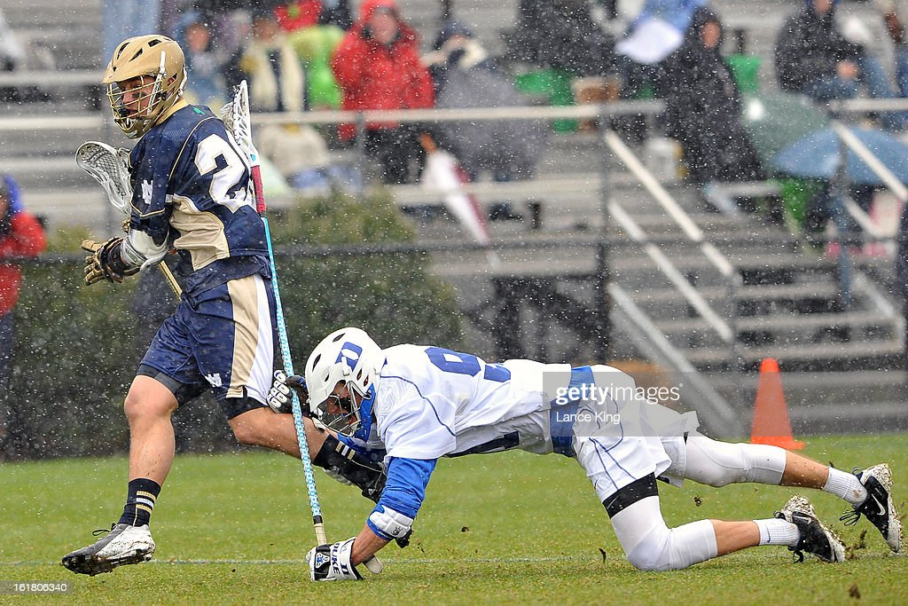 Luke Duprey #91 of the Duke Blue Devils falls while defending Nick Ossello #20 of the Notre Dame Fighting Irish at Koskinen Stadium on February 16, 2013 in Durham, North Carolina. Notre Dame defeated Duke 13-5.