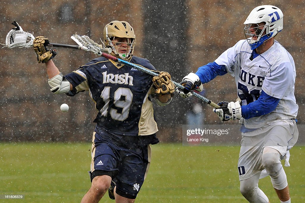 Luke Duprey #91 of the Duke Blue Devils knocks the ball away from Tyler Kimball #19 of the Notre Dame Fighting Irish at Koskinen Stadium on February 16, 2013 in Durham, North Carolina. Notre Dame defeated Duke 13-5.