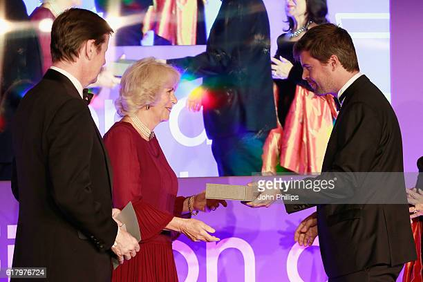 Luke Ellis and Camilla Duchess of Cornwall present shortlisted author David Szalay with a copy of his book 'All That Man Is' at the 2016 Man Booker...