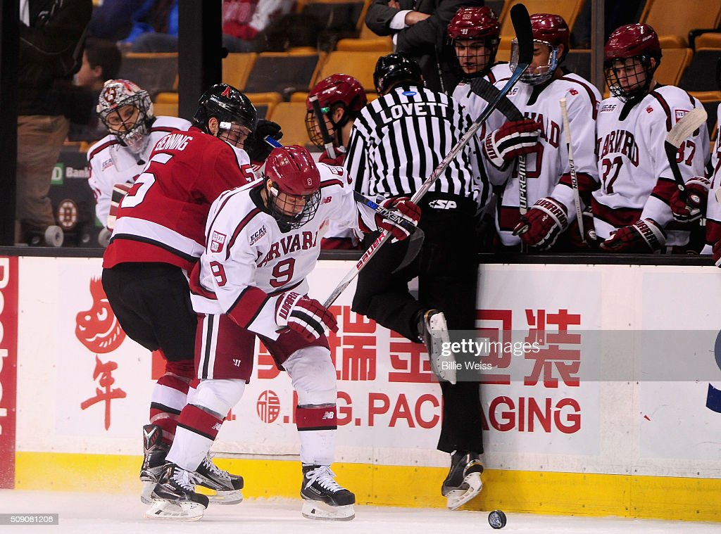 Luke Esposito #9 of Harvard University is hit by Matt Benning #5 of Northeastern University during the second period of the Beanpot Tournament consolation game at TD Garden on February 8, 2016 in Boston, Massachusetts.