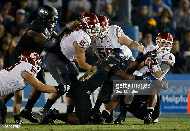 Luke Falk of the Washington State Cougars is sacked by Takkarist McKinley of the UCLA Bruins as Cole Madison of the Washington State Cougars Riley...