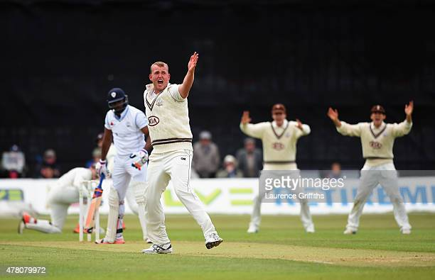Luke Fletcher of Surrey claims the wicket of Chesney Hughes of Derbyshire during the LV County Championship match between Derbyshire and Surrey at...