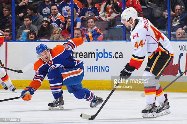Luke Gazdic of the Edmonton Oilers defends the shot of Chris Butler of the Calgary Flames during an NHL game at Rexall Place on December 7 2013 in...