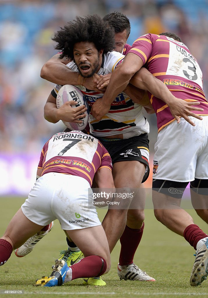 Luke George of Bradford Bulls is tackled by Luke Robinson and Leroy Cudjoe of Huddersfield Giants during the Super League match between Huddersfield Giants and Bradford Bulls at Etihad Stadium on May 18, 2014 in Manchester, England.
