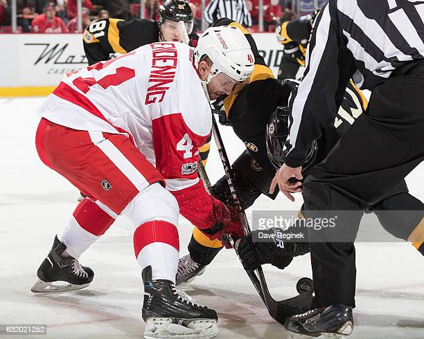 Luke Glendening of the Detroit Red Wings faces off against Dominic Moore of the Boston Bruins during an NHL game at Joe Louis Arena on January 18...