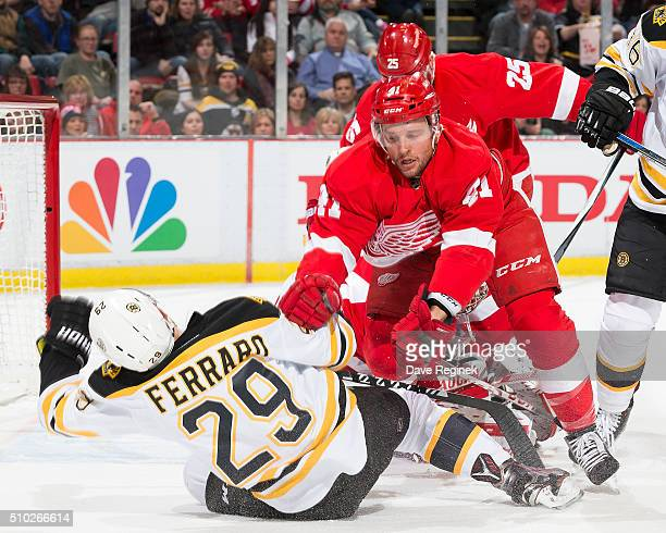 Luke Glendening of the Detroit Red Wings gets pushed into Landon Ferraro of the Boston Bruins during an NHL game at Joe Louis Arena on February 14...