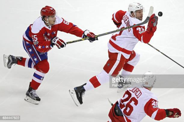 Luke Glendening of the Detroit Red Wings pulls in a loose puck with his hand as he is defended by Andre Burakovsky of the Washington Capitals during...