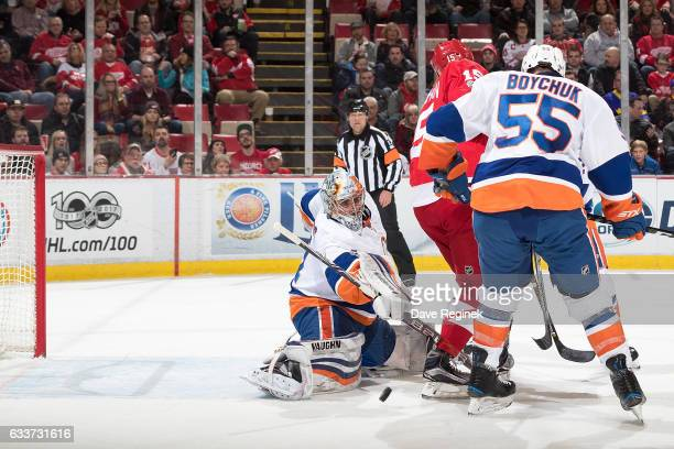Luke Glendening of the Detroit Red Wings scores a first period goal as teammate Riley Sheahan screens the view of goaltender Thomas Greiss of the New...