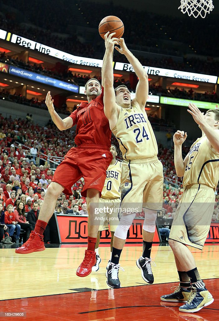 Luke Hancock #11 of the Louisville Cardinals and Pat Connaughton #22 of the Notre Dame Fighting Irish battle for a loose ball at KFC YUM! Center on March 9, 2013 in Louisville, Kentucky.