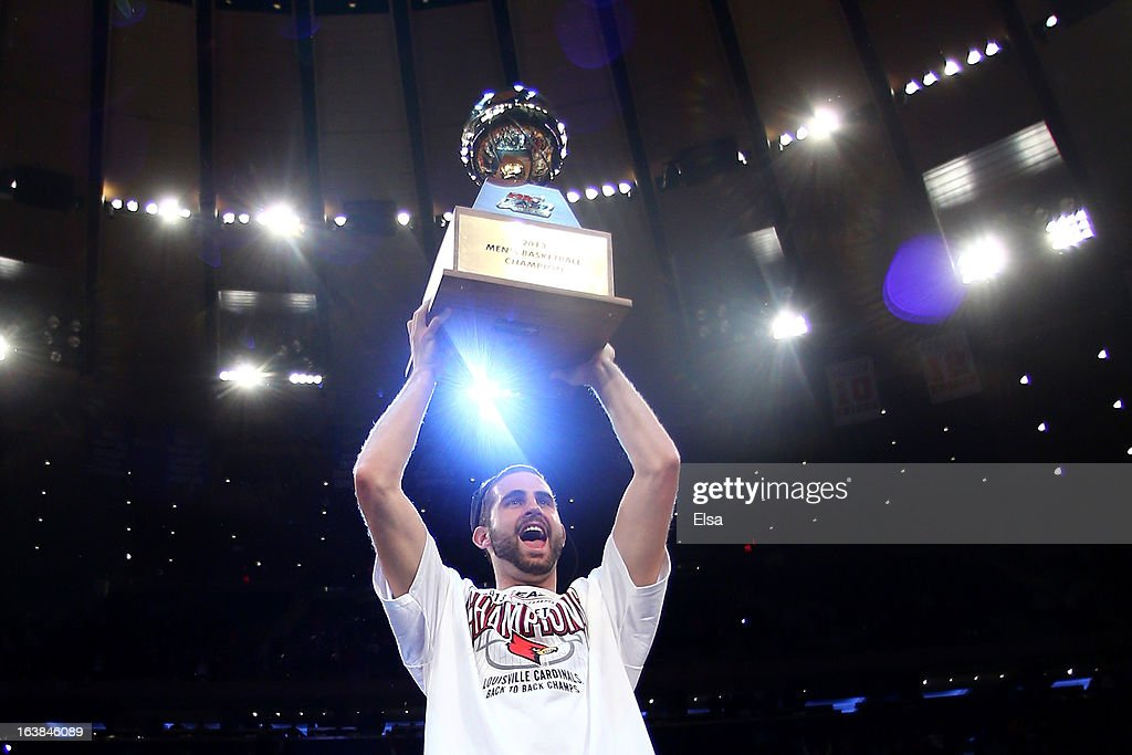 Luke Hancock #11 of the Louisville Cardinals celebrates with the conference championship trophy after they won 78-61 against the Syracuse Orange during the final of the Big East Men's Basketball Tournament at Madison Square Garden on March 16, 2013 in New York City.