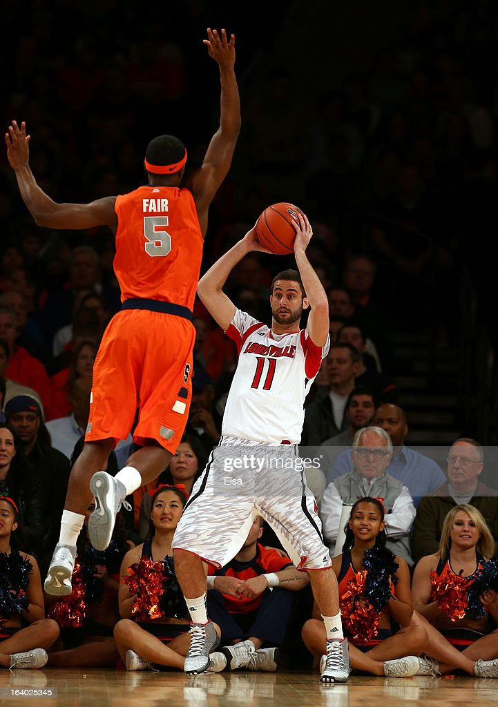 Luke Hancock #11 of the Louisville Cardinals looks to pass the ball against C.J. Fair #5 of the Syracuse Orange during the final of the Big East Men's Basketball Tournament at Madison Square Garden on March 16, 2013 in New York City.