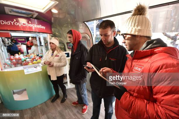 Luke Hicks shows patrons the Ebay app during a visit to the 'Did You Check eBay' Holiday Airstream at Christkindl Market on December 4 2017 in Denver...