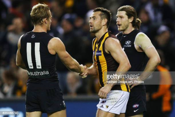 Luke Hodge of the Hawks hakes hands with a victorious Sam Kerridge of the Blues during the round 22 AFL match between the Carlton Blues and the...