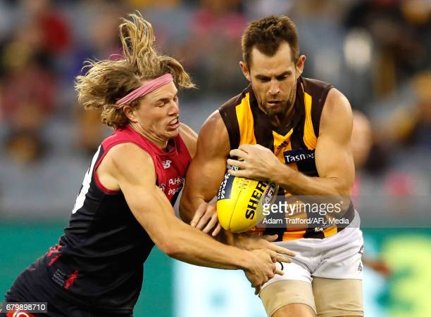 Luke Hodge of the Hawks is tackled by Jayden Hunt of the Demons during the 2017 AFL round 07 match between the Melbourne Demons and the Hawthorn...