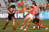 Luke Hodge of the Hawks smothers the kick of Andrew Boston of the Suns during the round nine AFL match between the Hawthorn Hawks and the Gold Coast...
