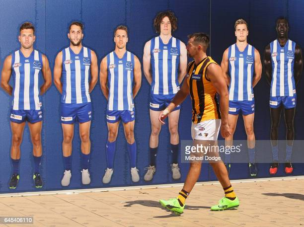 Luke Hodge of the Hawks walks past Kangaroos player portraits during the JLT Community Series AFL match between the North Melbourne Kangaroos and the...