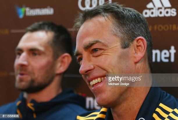 Luke Hodge reacts after announcing his retirement next to coach Alastair Clarkson on the eve of his 300th during a Hawthorn Hawks AFL press...