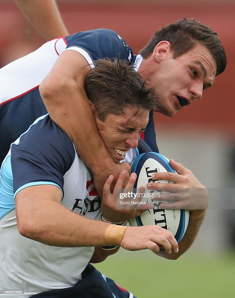 Luke Holmes of the Waratahs is tackled by Mitch Inman of the Rebels during the Super Rugby trial match between the Waratahs and the Rebels at North Hobart Stadium on February 2, 2013 in Hobart, Australia.