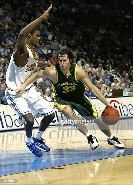 Luke Jackson of the Oregon Ducks drives around Trevor Ariza of the UCLA Bruins on January 4 2004 at Pauley Pavillion in Westwood California UCLA won...