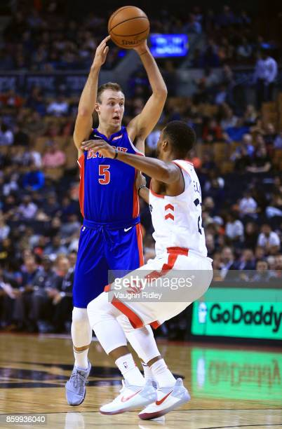 Luke Kennard of the Detroit Pistons passes the ball as Norman Powell of the Toronto Raptors defends during the first half of an NBA preseason game at...