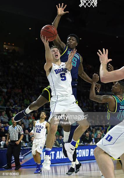 Luke Kennard of the Duke Blue Devils drives to the basket against Devontae Cacok of the North CarolinaWilmington Seahawks in the first half of their...